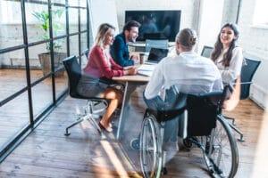 Réunion de travail avec une personne en fauteuil roulant